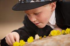 Menino novo que joga com flores Fotos de Stock