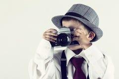 Menino novo que joga com uma câmera velha para ser fotógrafo Fotos de Stock Royalty Free