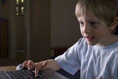 Menino novo que joga em um portátil Fotografia de Stock