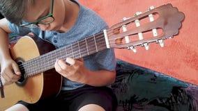 Menino novo que joga a guitarra video estoque