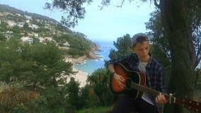 Menino novo que joga a guitarra acústica Guitarrista adolescente com instrumento musical video estoque