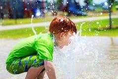 Menino novo que joga na água Fotografia de Stock