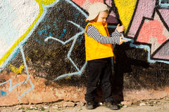 Menino novo que joga na frente dos grafittis coloridos Fotos de Stock Royalty Free