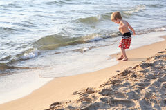 Menino novo que joga na praia Imagens de Stock Royalty Free