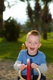 Menino novo que joga no parque em um dia ensolarado Fotografia de Stock