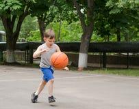 Menino novo que joga o basquetebol Imagens de Stock Royalty Free