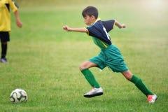 Menino novo que joga o futebol foto de stock royalty free