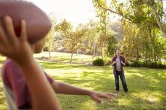 Menino novo que joga o futebol americano para seu paizinho no parque imagem de stock royalty free