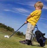 Menino novo que joga o golfe Fotografia de Stock