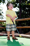 Menino novo que joga o mini golfe Fotos de Stock Royalty Free