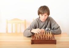 Menino novo que joga a xadrez Fotos de Stock