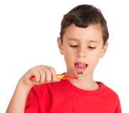 Menino novo que lambe a pasta de dente da escova dos dentes Foto de Stock Royalty Free