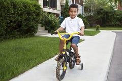 Menino novo que monta sua bicicleta Imagens de Stock Royalty Free