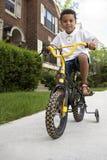Menino novo que monta sua bicicleta Fotos de Stock Royalty Free