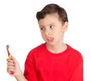 Menino novo que olha na maneira irritada a sua escova dos dentes Fotografia de Stock