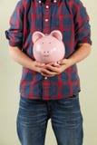 Menino novo que prende o banco Piggy cor-de-rosa Foto de Stock Royalty Free