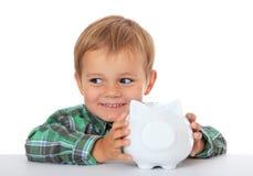 Menino novo que prende seu banco piggy Fotos de Stock Royalty Free