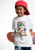 Menino novo que prende seu skate Fotografia de Stock