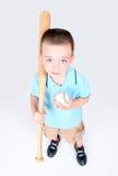Menino novo que prende um bastão de beisebol e uma esfera Fotografia de Stock