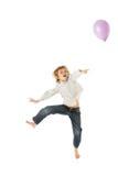Menino novo que salta com o balão no estúdio Imagens de Stock