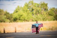 Menino novo que salta com uma bandeira americana que comemora o Dia da Independência fotografia de stock