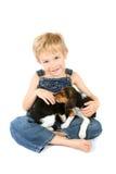 Menino novo que senta com os filhotes de cachorro do lebreiro em seu o regaço Fotografia de Stock Royalty Free