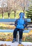 Menino novo que senta-se em um banco no parque com sua cara coberta Fotos de Stock