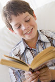 Menino novo que senta-se em um sofá que lê um livro Imagens de Stock Royalty Free