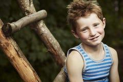 Menino novo que senta-se em uma escada de madeira, sorrindo Imagem de Stock