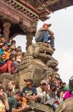 Menino novo que senta-se na escultura do leão
