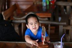 Menino novo que senta-se na tabela de madeira Imagens de Stock Royalty Free