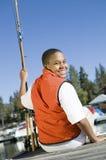 Menino novo que senta-se no cais com pesca Ros Foto de Stock Royalty Free