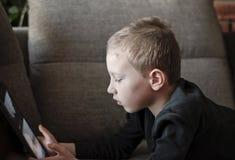 Menino novo que senta-se no sofá na sala de visitas e em desenhos animados de observação na tabuleta Retrato de uma criança esper fotografia de stock
