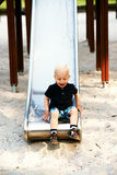 Menino novo que tem o divertimento em uma corrediça Foto de Stock