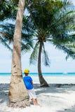 Menino novo que tem o divertimento em uma praia tropical com árvore de palmas Fotos de Stock Royalty Free