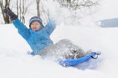 Menino novo que tem o divertimento na neve Fotografia de Stock Royalty Free