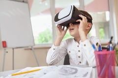 Menino novo que usa auriculares da realidade 3d virtual na escola imagens de stock royalty free