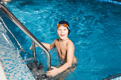 Menino novo que usa a escada para retirar a piscina Fotografia de Stock