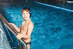 Menino novo que usa a escada para retirar a piscina Fotos de Stock Royalty Free