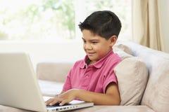 Menino novo que usa o portátil em casa fotos de stock royalty free
