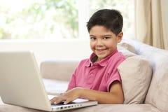 Menino novo que usa o portátil em casa fotografia de stock