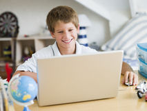 Menino novo que usa um portátil em seu quarto Fotos de Stock