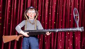 Menino novo vestido como o palhaço Holding Oversized Rifle Fotografia de Stock Royalty Free
