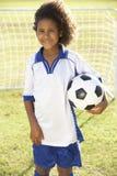 Menino novo vestido no futebol Kit Standing By Goal Fotos de Stock
