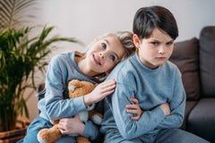 Menino ofendido de abraço da menina que senta-se no sofá em casa Fotos de Stock