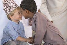 Menino omanense que faz frineds com menino europeu Imagens de Stock Royalty Free