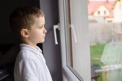 Menino pensativo da criança de 6 anos que olha para fora a janela Foto de Stock Royalty Free