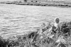 Menino pensativo louro que senta em um banco de rio no rochas Fotos de Stock