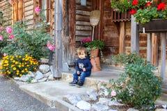 Menino pensativo pequeno bonito que senta-se no pátio de entrada coberto da casa de madeira do vintage velho cercada por flores foto de stock
