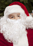 Menino pensativo vestido como Papai Noel Fotografia de Stock Royalty Free